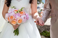 Bride and groom on wedding ceremony hold hands with wedding bouq. Uet from orange roses and pink peonies stock images