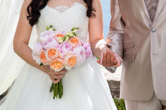 Bride and groom on wedding ceremony hold hands with wedding bouquet from orange roses and pink peonies. stock photos