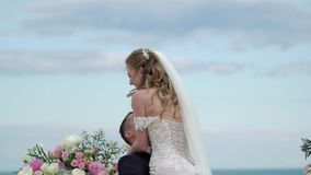 The bride and groom at the wedding ceremony. A young couple in love stands at the arch. Wedding by the sea stock video