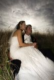 Bride and Groom on Wedding Day. A Bride and Groom sitting in tall grass under a dramatic, cloudy sky on their wedding day Stock Photo