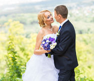 Bride and groom at wedding Day walking Outdoors. Happy Newlyweds  embracing. Loving couple. Royalty Free Stock Photography