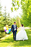 Bride and Groom at wedding Day walking Outdoors on spring nature. Bridal couple, Happy Newlywed woman and man embracing Royalty Free Stock Photography