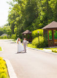 Bride and Groom at wedding Day walking Outdoors on spring nature. Bridal couple, Happy Newlywed woman and man embracing Royalty Free Stock Photos