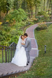 Bride and groom at wedding Day walking Outdoors on spring nature. Bridal couple,. Happy Newlywed women and men embracing in green park. Loving wedding couple Stock Image