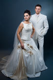 Bride and groom in wedding dress. Happy bride and groom posing together in studio, wearing wedding dress, smiling Royalty Free Stock Images