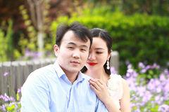 Bride and groom in wedding dress with elegant hairstyle, with white wedding dress Sitting on the bench next to the fence Stock Photography