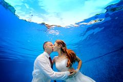 The bride and groom in wedding dresses embrace and kiss underwater in the pool on a blue background. Close-up. Landscape orientation. Shooting underwater in Royalty Free Stock Photo