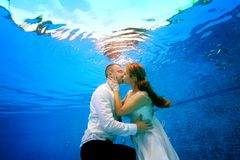 The bride and groom in wedding dresses kissing underwater in the swimming pool. Portrait. Shooting underwater. The bride and groom in wedding dresses kissing Royalty Free Stock Photography