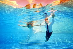 The bride and groom in wedding dresses swim underwater in the pool in my direction on the background of a tropical sunset. Shooting under water. Landscape Royalty Free Stock Photography