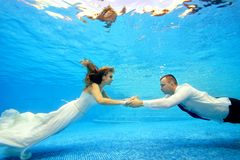 The bride and groom in wedding dresses swim underwater in the pool to meet each other. Portrait. Landscape orientation. Shooting under water Royalty Free Stock Photography