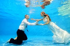 The bride and groom in wedding dresses swim underwater in the pool to meet each other. Portrait. Shooting under water. Landscape orientation Stock Images