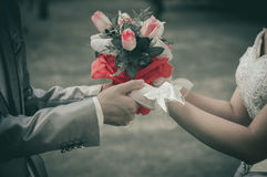 Bride and groom wedding flowers in hand - sepia tone Royalty Free Stock Photos