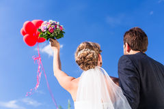 Bride and groom at wedding with helium balloons Royalty Free Stock Image