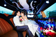 Bride and groom in wedding limo. Usine with yellow and black colors Royalty Free Stock Photos