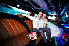 Bride and groom in wedding limo. Usine with glasses of champagne Stock Image