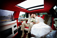 The bride and groom in a wedding limousine Stock Photos