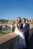 Bride and groom wedding poses on the bank of the river Tiber loo Royalty Free Stock Image