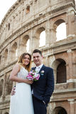 Bride and groom wedding poses in front of Colosseum, Rome, Italy Royalty Free Stock Photo