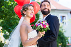 Bride and groom at wedding with read helium balloons Royalty Free Stock Photo