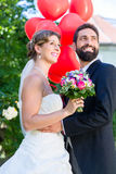 Bride and groom at wedding with read helium balloons Royalty Free Stock Image