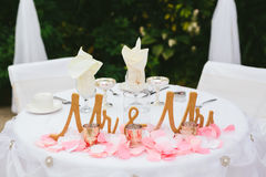 Bride and Groom wedding reception table decor. A romantic bride and groom wedding reception head table for two with a pink and gold color scheme. Garden wedding Royalty Free Stock Image