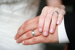 Bride and Groom Wedding Rings. Bride and Groom showing off their new wedding rings on their hands with the bride's dress in the background Royalty Free Stock Image