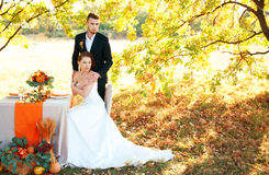 Bride and groom at the wedding table. Autumn outdoor setting. Royalty Free Stock Photography