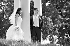 Bride and groom at wedding walk around column Stock Photos