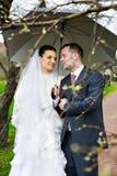 Bride and groom at wedding walk with umbrella Stock Photos