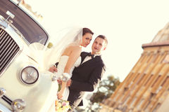 Bride and groom with a white retro car Royalty Free Stock Photo