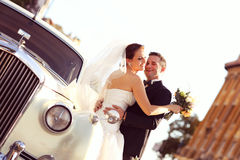 Bride and groom with a white retro car Royalty Free Stock Images