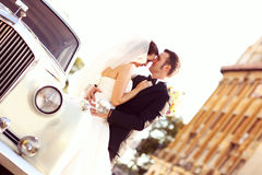 Bride and groom with a white retro car
