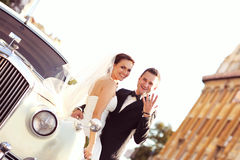 Bride and groom with a white retro car Royalty Free Stock Photos