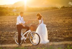Bride and groom with a white wedding bike. Beautiful bride and groom wedding portrait with white bike Royalty Free Stock Photography