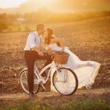 Bride and groom with a white wedding bike. Beautiful bride and groom wedding portrait with white bike Stock Image