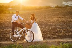 Bride and groom with a white wedding bike stock image