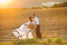 Bride and groom with a white wedding bike. Beautiful bride and groom wedding portrait with white bike Royalty Free Stock Images