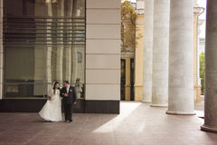 Bride and groom wlaking at historical place. Happy young justmarried couple walking at historical colonnade Stock Image