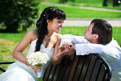 Bride and groom on wooden bench Stock Image