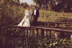 Bride and groom on wooden bridge Stock Images