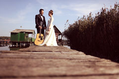 Bride and groom on wooden bridge near houses on lake Royalty Free Stock Photos