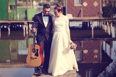 Bride and groom on a wooden bridge near lake Royalty Free Stock Image