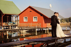 Bride and groom on a wooden bridge near lake Stock Photography