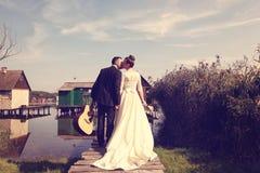 Bride and groom on wooden bridge near lake Stock Image