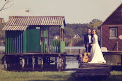 Bride and groom on wooden bridge near lake Royalty Free Stock Images