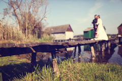 Bride and groom on wooden bridge near lake Stock Photo
