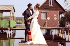 Bride and groom on a wooden bridge near lake Royalty Free Stock Photography