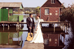 Bride and groom on a wooden bridge near lake Royalty Free Stock Photo