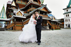 Bride and groom about the wooden palace Royalty Free Stock Images
