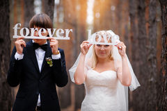 Bride and groom in the woods with an inscription in the hands Stock Photography